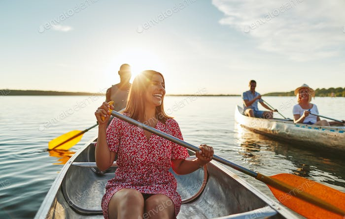 Laughing woman canoeing with friends on a late summer afternoon
