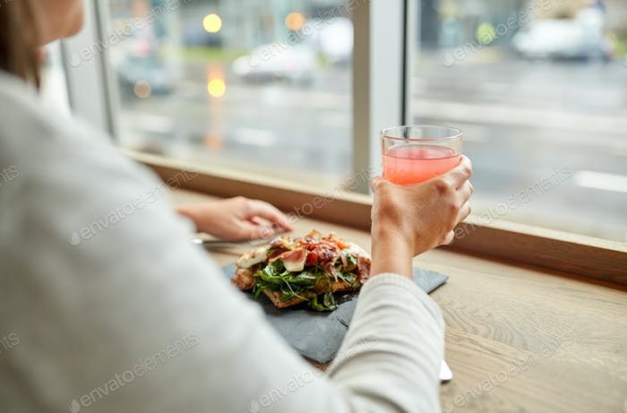 woman with salad and glass of drink at restaurant
