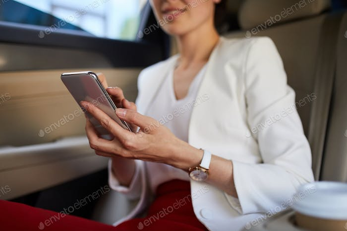 Woman Using Smartphone in Car