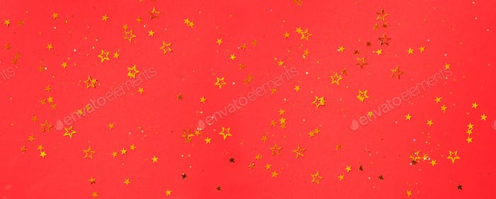 Golden star sparkles on red background. Christmas and New year concept. Festive backdrop with copy