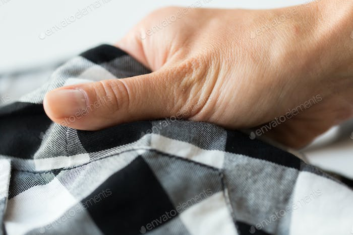 close up of hand with checkered clothing item