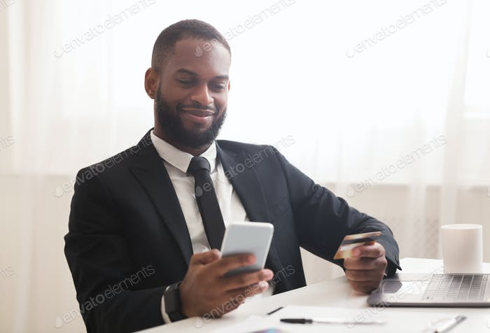 Afro businessman holding credit card, making purchases online by phone