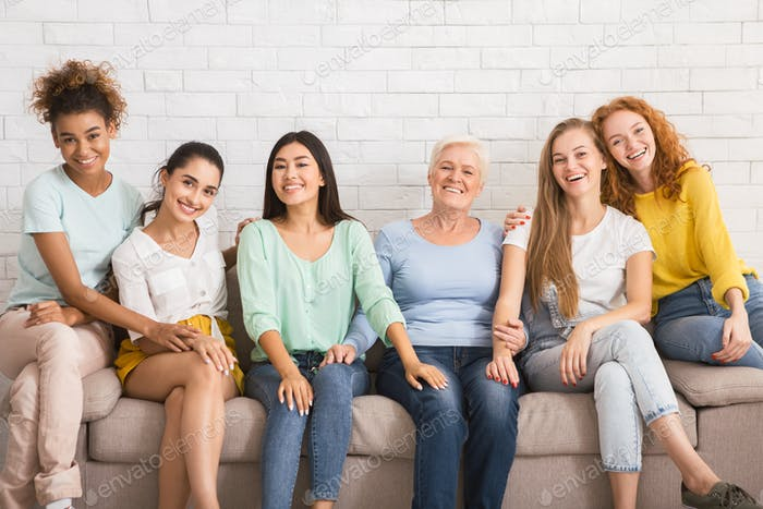 Group Of Women Smiling Sitting On Couch Against White Wall