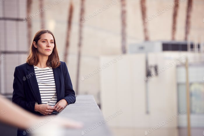 Portrait Of Thoughtful Businesswoman Standing Outside Modern Office Building