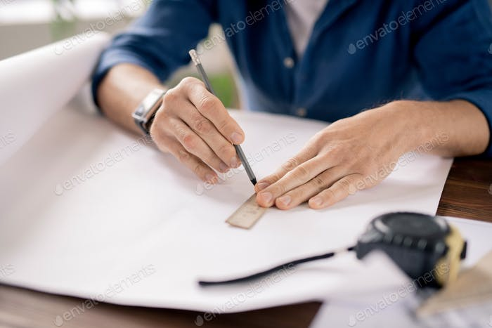 Hands of mature engineer holding pencil and ruler while drawing line on paper