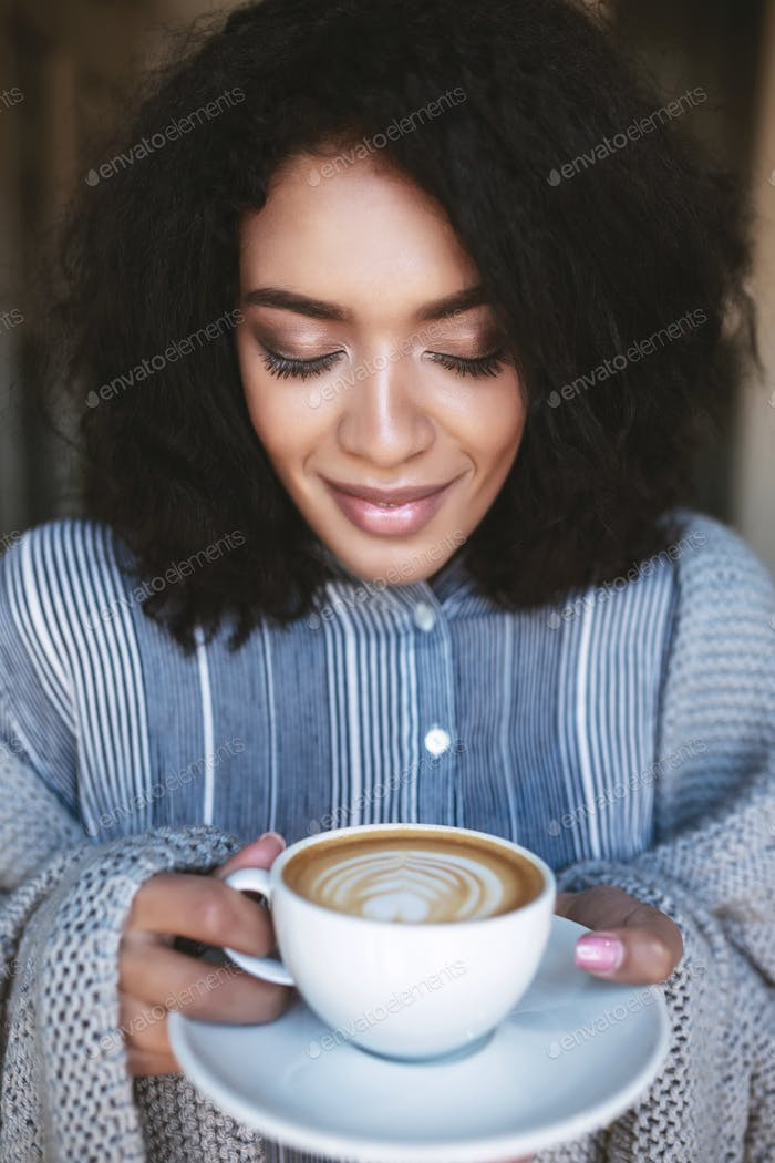 Portrait of beautiful African American girl with cup of cappuccino in hands