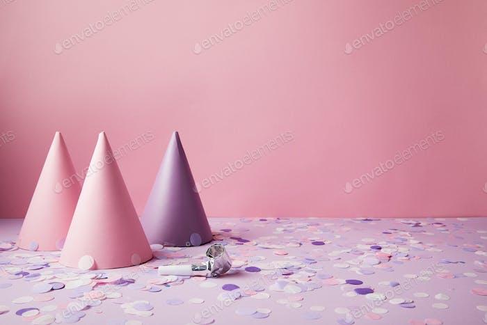 rosa und violette Partyhüte und Konfetti Stücke auf violetter Tischplatte