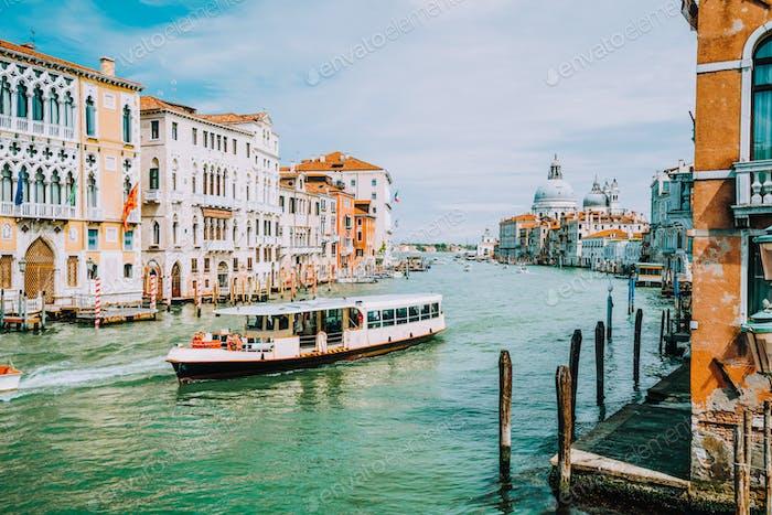 Local transportation boat at Grand Canal. Basilica Santa Maria della Salute in background, Venice