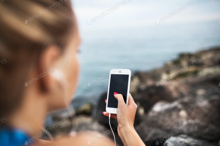 Young sporty woman runner with earphones and smartphone sitting on rocks by sea.