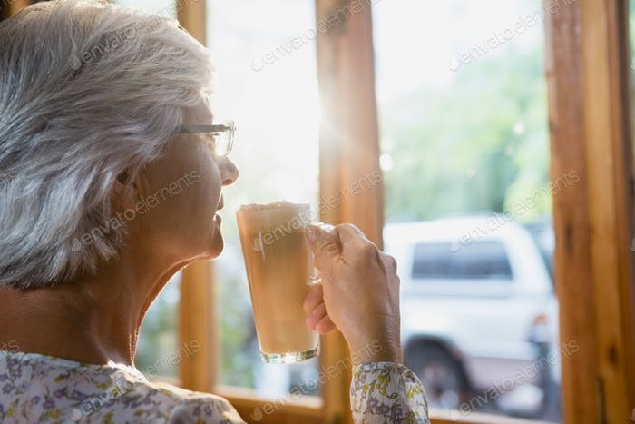 Thoughtful senior woman having coffee
