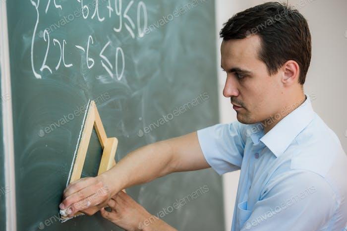 Junge Lehrer oder Schüler zeichnen Dreieck auf einer Tafel mit Formel