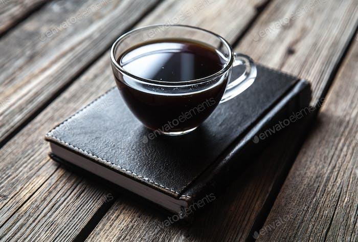 schwarzes Buch und eine Tasse Kaffee auf einem hölzernen Hintergrund