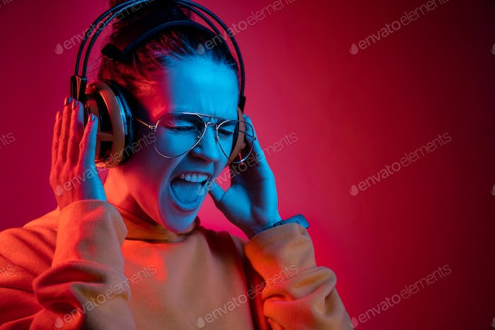 Fashion pretty woman with headphones listening to music over neon background