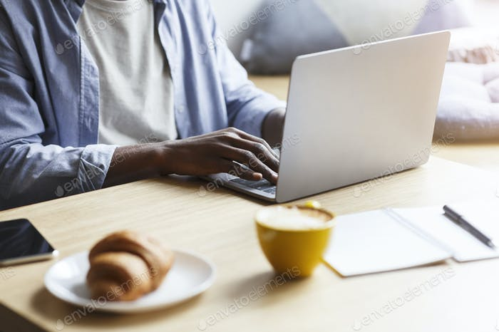 African American blogger working with laptop while having breakfast in cafe, closeup