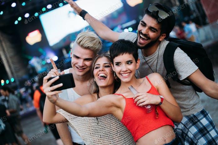 Glückliche Freunde nehmen Selfie auf Musikfestival