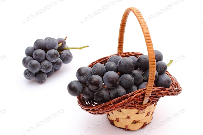 Fresh and natural grapes in wicker basket on white background