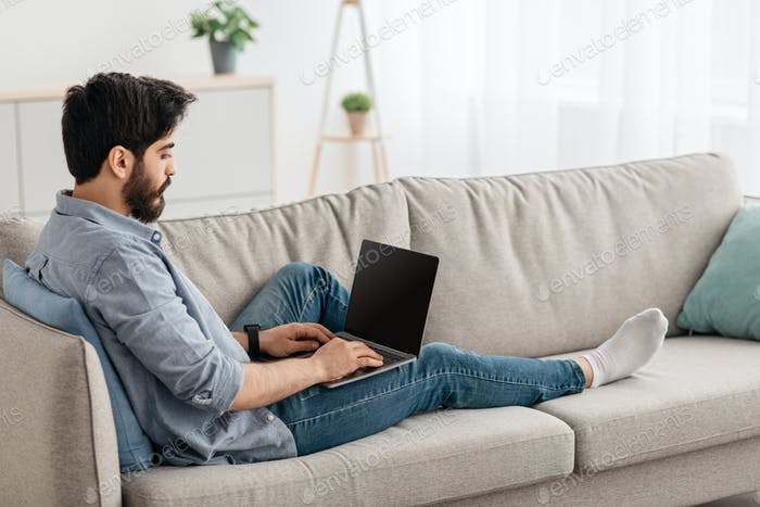 Relaxed arab man using laptop with blank screen, resting on couch in living room, home interior