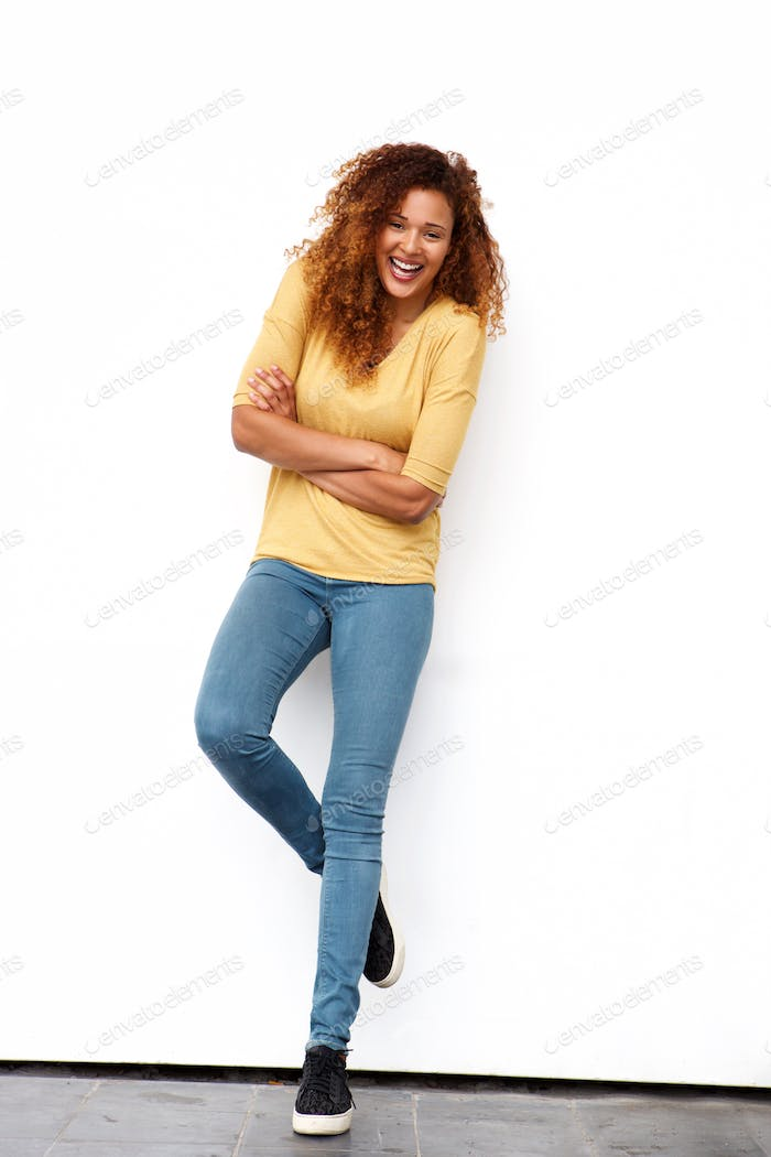 Full body happy young woman with curly hair against white wall