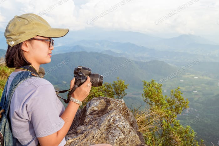 Hiker teen girl holding a camera for photography