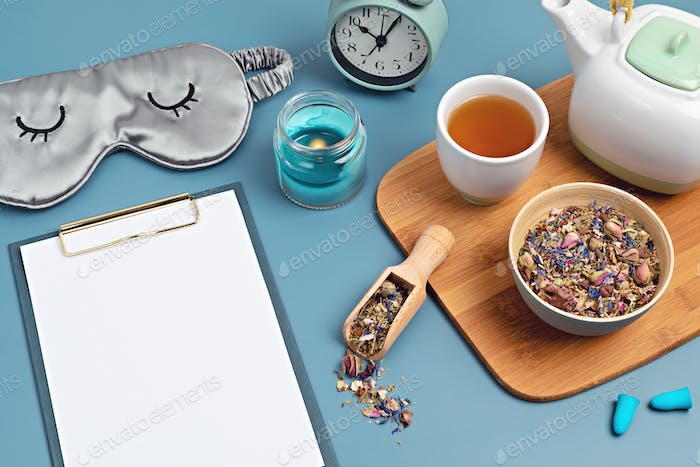 Classic alarm clock, sleeping mask, clipboard and herbal tea. Minimal concept of rest, quality of