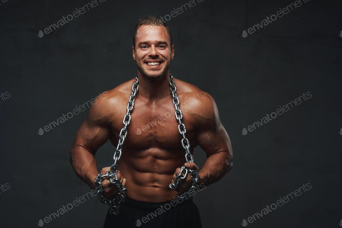 Guy with perfect body posing with chains in studio