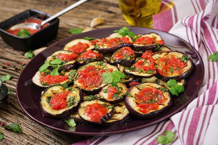 Eggplant grilled with tomato sauce, garlic, cilantro and mint. Vegan food. Grilled aubergine.