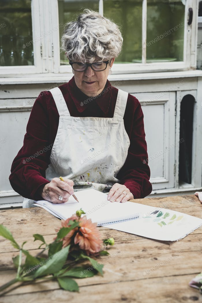 Senior woman wearing glasses, red dress and white apron sitting at table, working on pencil drawing
