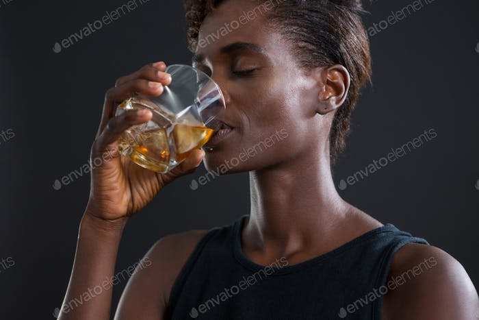 Androgynous man drinking whiskey from glass