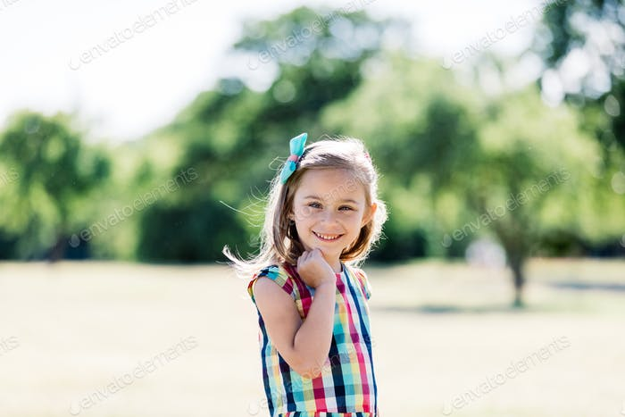 A young happy girl in colorful checkered dress standing in the park,
