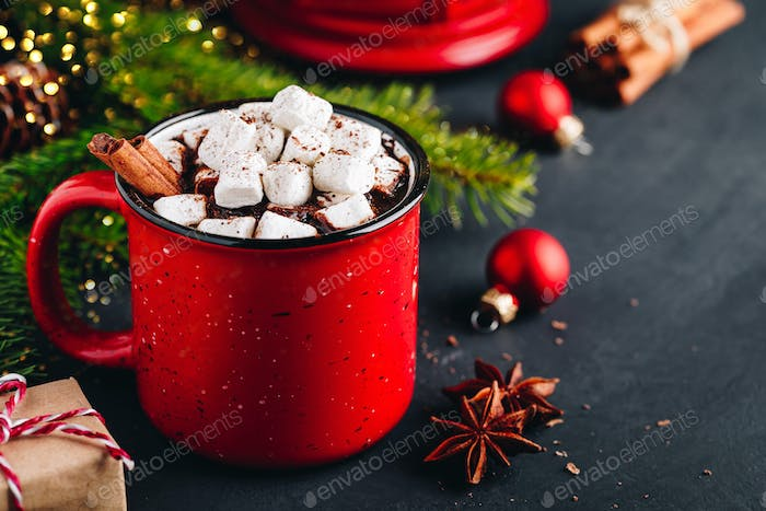 Christmas winter drink Hot Chocolate with marshmallow and cinnamon stick in red mug