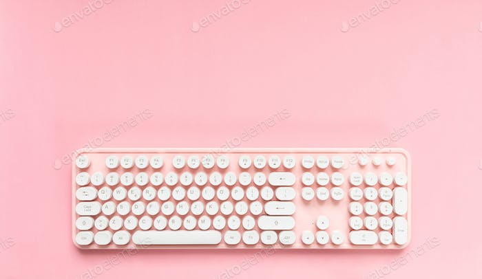 Computer keyboard isolated against pink background
