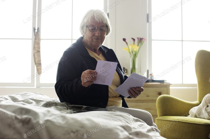 Senior woman sitting on the bed and looking at photos