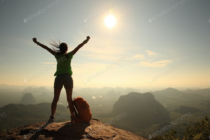 Cheering for see the first sight sunshine on mountain top