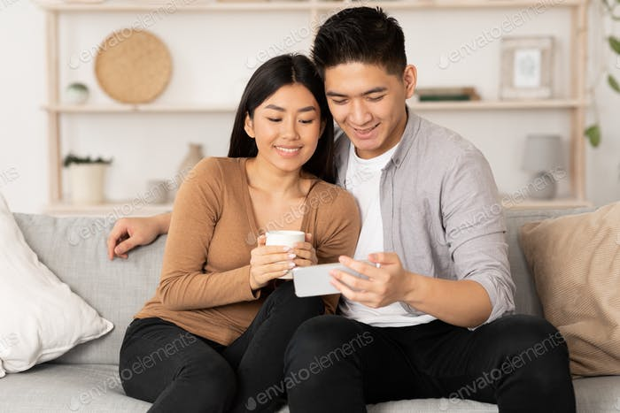 Korean couple resting at home, using phone