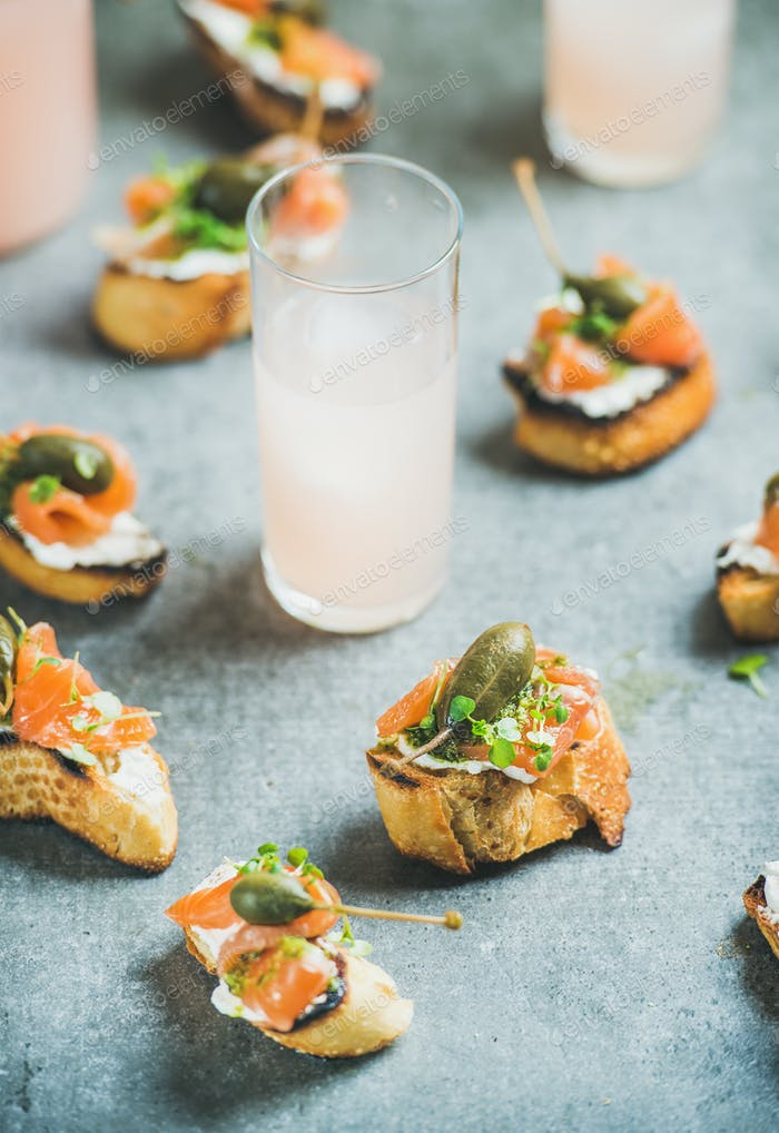 Crostini with smoked salmon and grapefruit cocktails, selective focus