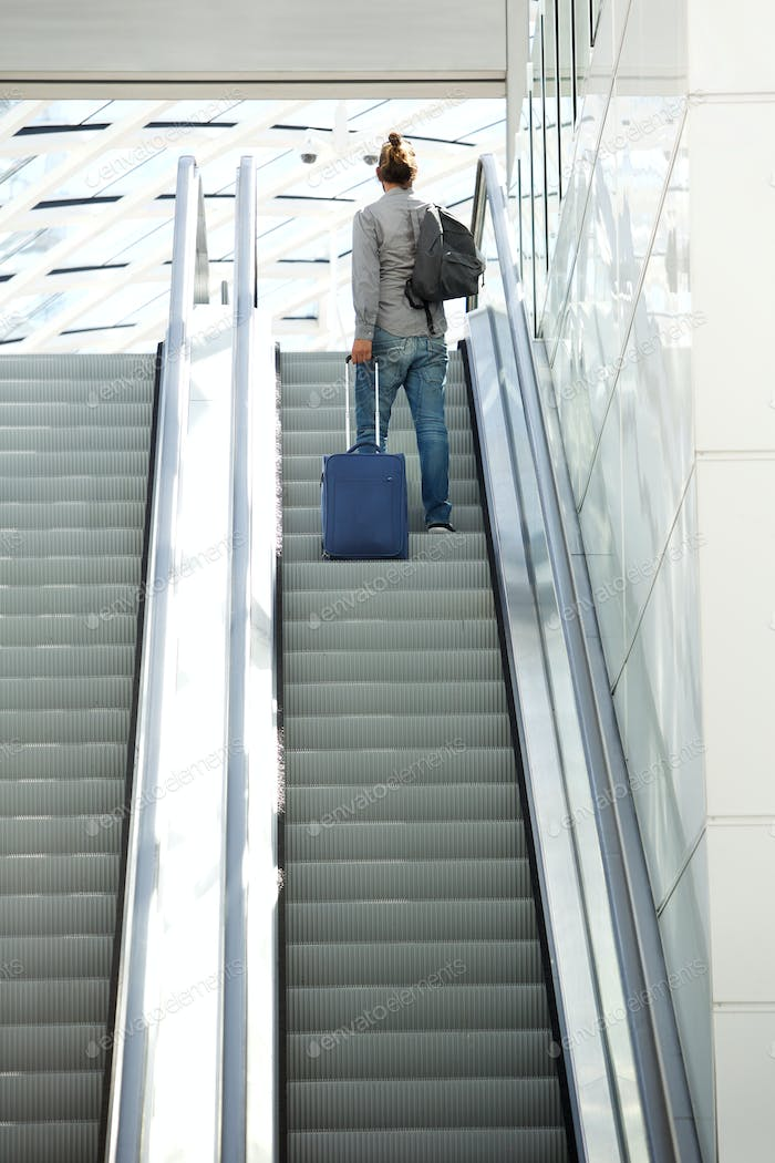 Man standing on escalator with travel bags