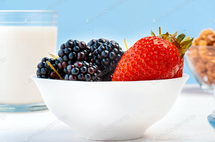 Fresh berries in glass pot.