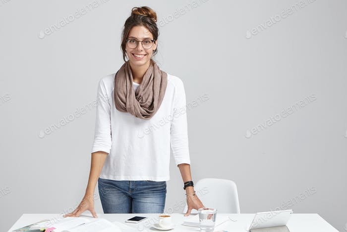 Portrait of talented female freelancer, works remotely, uses modern technologies, leans hands on des