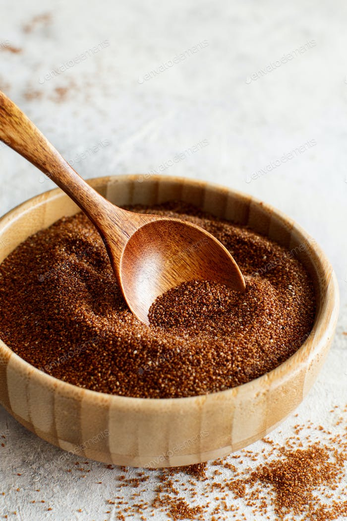 Uncooked teff grain in a bowl with a wooden spoon close up