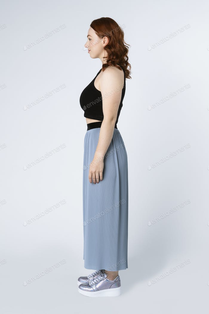 Woman wearing a crop top and skirt pants in a profile shot