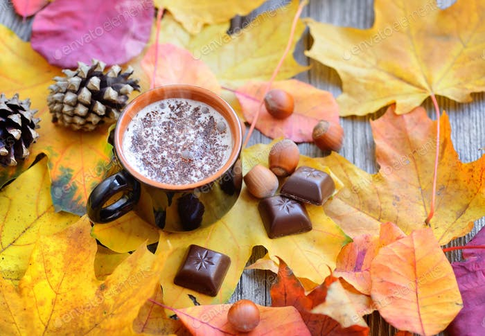 Autumn Cup of coffee, nuts, pine cones, chocolate and autumn lea