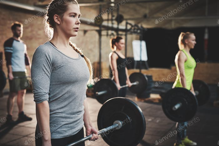 Woman in class doing dead lift barbell exercise