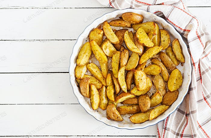 Ruddy Baked potato wedges with garlic on a white background. Flat lay. Top view.