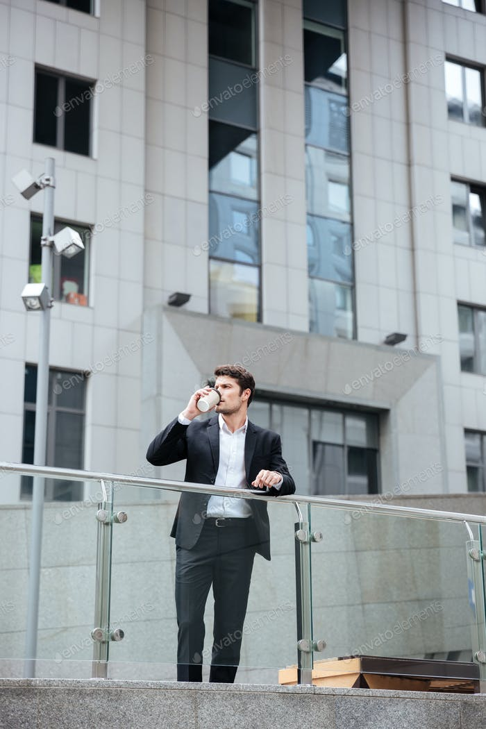Businessman standing and drinking coffee near business center