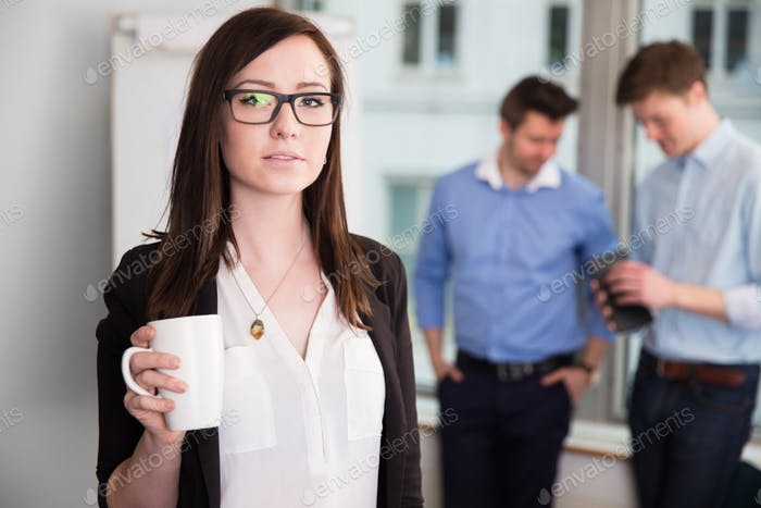 Businesswoman Holding Coffee Mug While Colleagues Discussing In