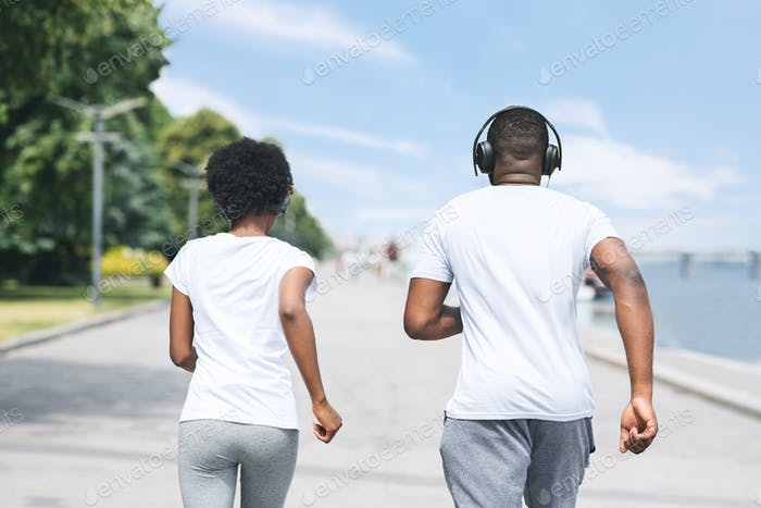 Unrecognizable Afro Couple Jogging Along River Embankment