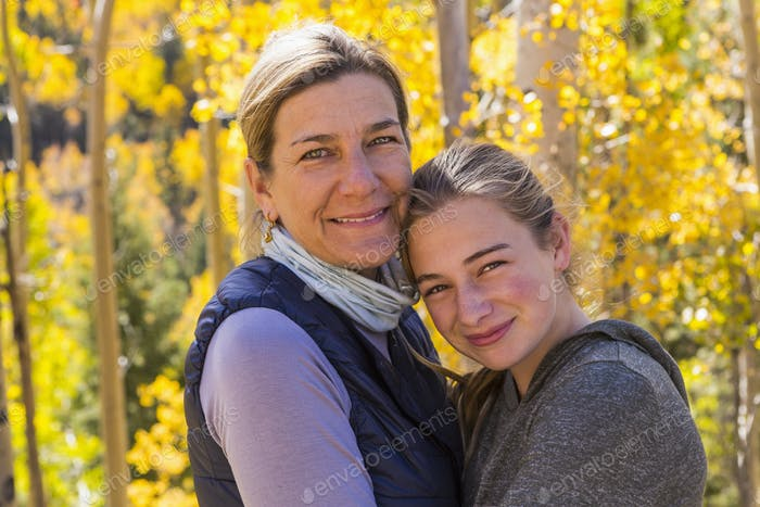 portrait of mother and her 13 year old daughter with autumn aspens in background