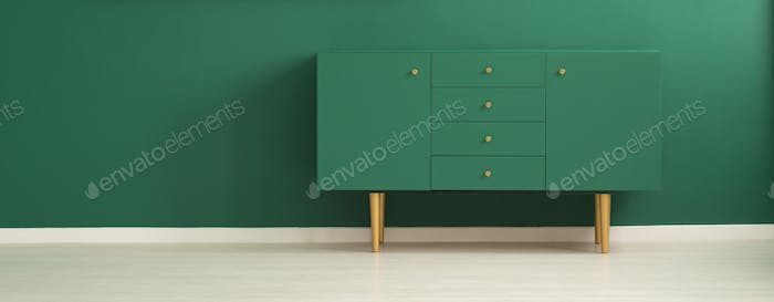 Modern sideboard in green interior