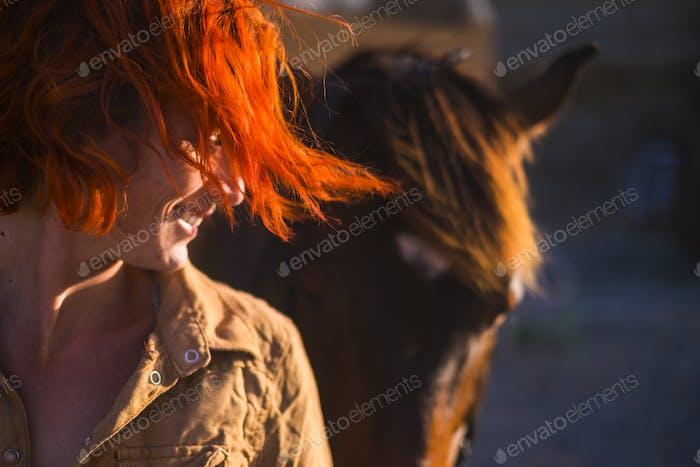 pelo rojo hermoso estilo de vida mujer joven con mejor amigo caballo