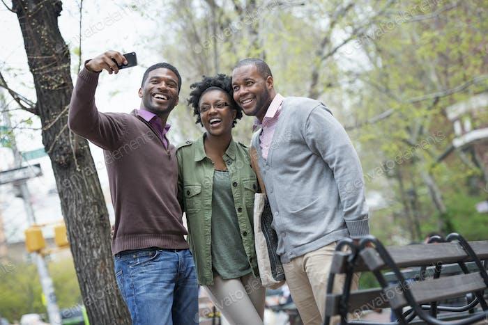 Im  Frühling im Freien in der Stadt. Drei Leute nehmen ein Selfie mit einem Smartphone.